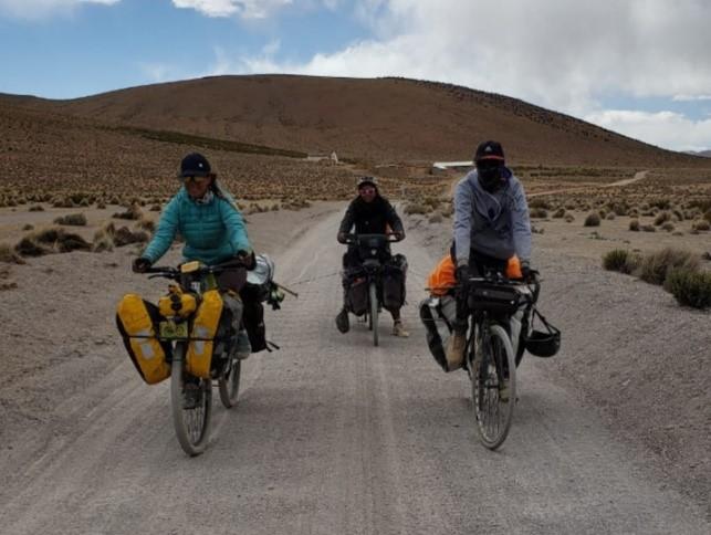 Dans le désert, 2 vélos remorquent un 3ème